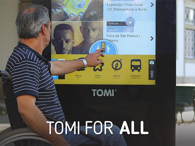 A man in a wheelchair touching a screen