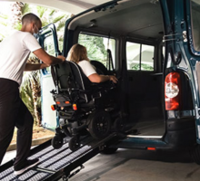 Wheelchair user entering minivan with assistance