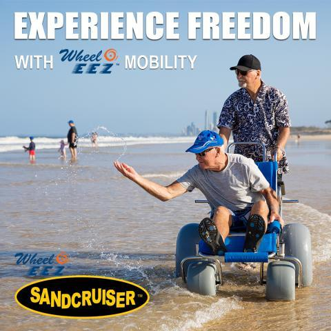 Wheeleez beach wheelchair on beach with older man seated and another pushingand
