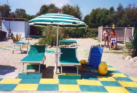 Two adapted sunbeds on a paved beach with a blue and yellow beach wheelchair next to them under an umbrella