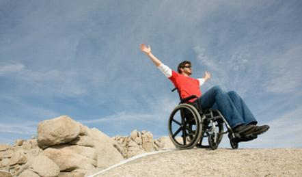 Male wheelchair user on rock with widespread arms